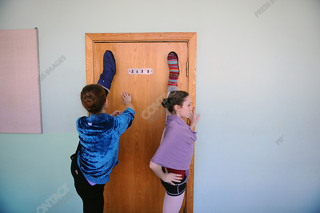 Girls in the class of Joy Womack, an American student at the Moscow State Academy of Choreography, the main school feeding dancers to the Bolshoi Ballet and one of the top ballet schools in the world, warmed up in the corridor before a class. Moscow, Russia, March 10, 2010