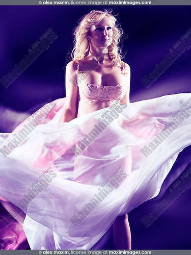Beautiful woman surrounded by flying in the wind fabrics on blue background