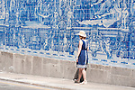 A woman in a build dress and a straw hat walks by tiled walls of the Capela das Almas in Porto, Portugal.