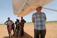 UGANDA Karamoja, airstrip Kotido, Missionary of Mill Hill missionaries Ireland, young Karimojong and Cessna aircraft of MAF Mission Aviation Fellowship which works for christian missions, NGOs, organizations to transport people and relief goods / UGANDA Karamoja, airstrip Kotido, Missionar, Karimojong und Cessna der MAF Mission Aviation Fellowship ist ein christlicher Flugdienst, der fuer christliche Missionswerke , NGOs , Organisationen  fliegt