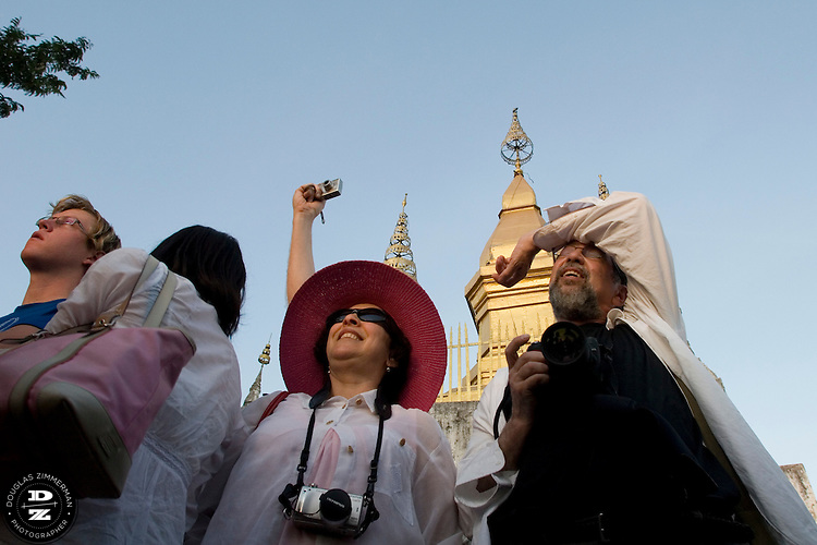 Tourists react to watching the sunset at Phu Si Hill or Chomsy Hill in central Luang Prabang, Laos. The hill is a popular place for tourists and locals to view the sunset over the hills surrounding the city.  Photograph by Douglas ZImmerman.