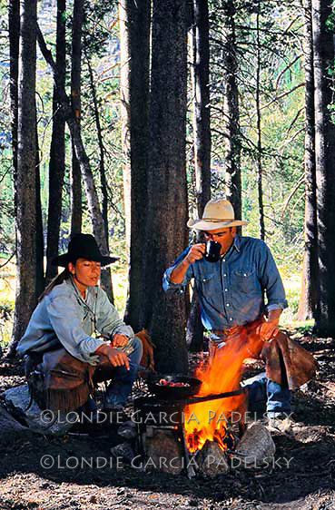 Cowboy and cowgirl cooking breakfast over  a campfire in the Kings Canyon National Park,California (Heidi and Ron Garcia)