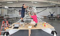 NWA Democrat-Gazette/J.T. WAMPLER Manuel Burgos (left) of Bentonville and Chris Landis of Bella Vista work on a Cessna Caravan equipped with floats Tuesday August 18, 2015 at a Summit Aviation hanger at the Bentonville Municipal Airport. <br /> Today (AUGUST 19) is National Aviation Day, established by Franklin D. Roosevelt in 1939. Summit Aviation does plane repair, maintenance, and flight training.