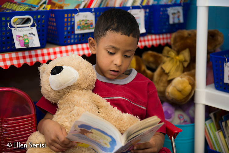MR / Schenectady, New York. Yates Arts-in-Education Magnet School (urban public school). First grade classroom. Student (boy, 6, Puerto Rican) reading book in reading corner at free playtime. MR: Igu1. ID: AM-g1w. © Ellen B. Senisi.