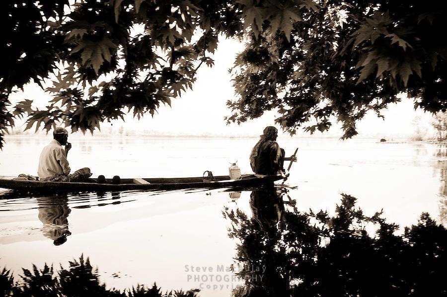 Man and woman paddling traditional shikara on Dal Lake, Srinagar, Kashmir, India.