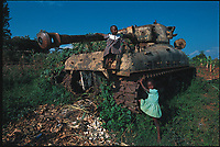 Young girls playing on an army tank abandoned by Idi Amin's army. Kampala, Uganda