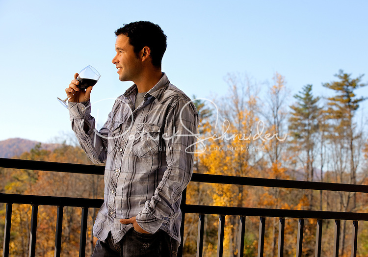 A man, holding a glass of wine, looks out over the Blue Ridge Mountains from a balcony in Asheville NC's Biltmore Park Town Square, a planned community of residential living, office spaces and shopping.