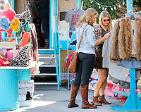 NWA Democrat-Gazette/DAVID GOTTSCHALK  Taylor Kline (left) and Jessica Heard look through items available from the mobile boutique of Whimsy & Whoo of Springdale Friday, November 6, 2015, during the Northwest Arkansas Boutique Show at the Springdale Convention Center. More than 140 merchants are participating in the event which continues today with a portion of the proceeds going towards the Junior League of Northwest Arkansas and the Fayetteville Junior Civic League.