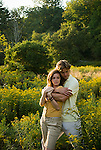 Couple embracing in open field