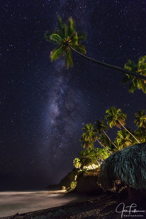 The Milky Way and palm trees at night, Dominican Republic..  The palms are lit with artificial lights.