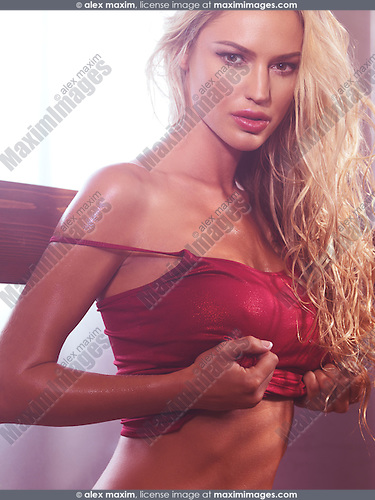 Sensual portrait of a sexy young woman with long blond hair taking her shirt off