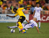 Dennis Alas (14) of El Salvador tackles the ball away from Darren Mattocks (17) of Jamaica at RFK Stadium in Washington, DC.  Jamaica defeated El Salvador, 2-0.
