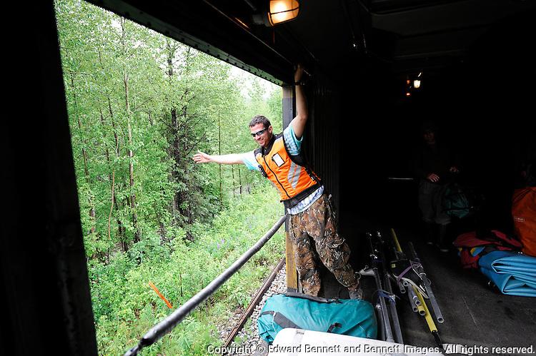 Conductor Charles Baldwin waves to a homesteader along the Alaska Railroad north of Talkeetna. The Alaska Railroad's Hurricane Turn is one of America's last true whistlestop trains.