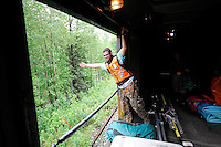 Conductor Charles Baldwin waves to a homesteader along the Alaska Railroad north of Talkeetna. The Alaska Railroad's Hurricane Turn is one of America's last true whistlestop trains.