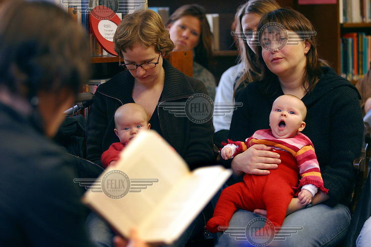 """Three month old Jenny struggles to stay awake as her mother Marit Helland listens to a book reading. An activity aimed at the parents rather than the babies, libraries invite authors to read on special """"book 'n' baby"""" days..In contrast to most European countries, the Norwegian birth rate is a healthy 1.9. Norway's reputation as a child friendly society is partially founded on a succession of government initiatives to improve parents' rights and economic circumstances."""