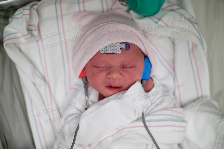 Newborn Infant baby girl minutes after birth in hospital hearing test