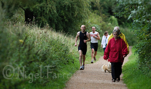 17 AUG 2011 - NORWICH, GBR - Iain Dawson (left) avoids walkers during a Tri-Anglia club aquathlon at Whitlingham Outdoor Centre. Through reconnoitering courses in advance with his wife Jill and then memorising landmarks they find he can race independently in shorter, less crucial, events though can have difficulty with low branches and obstacles on paths such as dogs  (PHOTO (C) NIGEL FARROW)