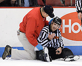 Larry Venis (BU - Trainer) tends to Bob Bernard who was struck by a puck. - The visiting University of Vermont Catamounts tied the Boston University Terriers 3-3 in the opening game of their weekend series at Agganis Arena in Boston, Massachusetts, on Friday, February 25, 2011.