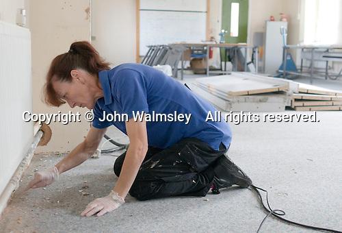 Premises staff refurbishing a room,  State Secondary Roman Catholic school.
