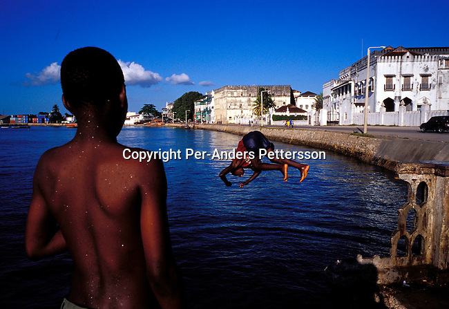 dicotanz00063 .Tanzania. Children. Boys swimming in the sea by the waterfront on October 8, 2002 in Stone Town, Zanzibar, Tanzania. Zanzibar has become a popular tourist destination due to the beautiful virgin beaches and influence of Arabic, Indian and African cultures on the Island. .©Per-Anders Pettersson/iAfrika Photos..