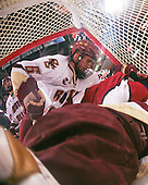Benn Ferriero (BC 21) and an official look on as Tim Kunes (BC 6) and Matt McCollem (Harvard 23) join John Muse (BC 1) in the net. The Boston College Eagles defeated the Harvard University Crimson 6-5 in overtime on Monday, February 11, 2008, to win the 2008 Beanpot at the TD Banknorth Garden in Boston, Massachusetts.