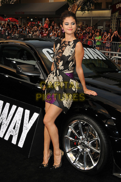 Selena Gomez<br /> &quot;Getaway&quot; Los Angeles Premiere held at the Regency Village Theatre, Westwood, California, USA.<br /> August 26th, 2013<br /> full length black white floral print dress sleeveless structured purple lace panel car leaning <br /> CAP/ADM/BP<br /> &copy;Byron Purvis/AdMedia/Capital Pictures