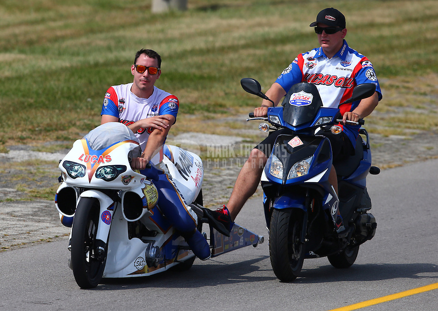 Aug. 31, 2013; Clermont, IN, USA: NHRA pro stock motorcycle rider Adam Arana (left) with a crew member during qualifying for the US Nationals at Lucas Oil Raceway. Mandatory Credit: Mark J. Rebilas-