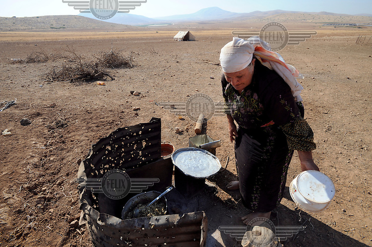 A woman cooks on a makeshift stove at the family's encampment in the Hadidiyeh area in the Jordan Valley. Bedouin living in the Hadidiyeh area which lies close to the Israeli settlement of Ro'ee and in a declared military fire zone, are threatened with eviction orders issued by Israeli authorities.