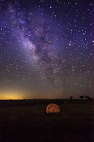 Stars at the Farm - Another capture as a verticle capture of the night skies star filled landscape with of the milky wayover a hay bales on this rural landscape in the Texas hill country. The bales of hay were painted in a gold light in the forground of the image to add the feel of this country night landscape.