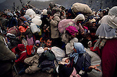 Isikveren, Turkey.April 16, 1991..Kurdish families, being detained by well armed Turkish soldiers, wait to be transported from a mountain top refugee camp. The camp became home to an estimated 300,000 refugees when they fled Saddam Hussein's post Gulf war persecution...In the wake of the 1991 Persian Gulf War rebellions in Southern and Northern Iraq occurred. The uprising in the Kurdish areas of Northern Iraq broke out in March, sparked by demoralized Iraqi Army troops returning from it's defeat against United States lead coalition forces in southern Iraq and Kuwait. Although they presented a threat to Iraqi President Saddam Hussein?s regime, his Iraqi Republican Guard suppressed the rebellion with massive force, as the expected US intervention never materialized. ..The faltering rebellion fueled a terrified mass exodus. The U.N. High Commissioner for Refugees called it the largest in its 40?year history. During March and early April, nearly two million of Iraqis escaped from strife-torn cities to the mountains along the northern borders and into Turkey and Iran. Their exodus was sudden and chaotic, with thousands fleeing on foot, on donkeys, or crammed onto open-backed trucks and tractors. Thousands, many of them children, died or suffered injury along the way, primarily from adverse weather, unhygienic conditions and insufficient food and medical care. Some were killed by army helicopters, which deliberately strafed columns of fleeing civilians. Others were injured when they stepped on land mines planted by Iraqi troops near the Iran border during the war. Greenpeace has estimated that at one point in 1991, an estimated 2,000 Kurds were dying every day..