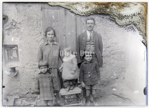 severely eroding glass plate photo with family posing infront of their house