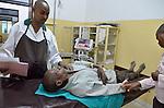 Treating a machete gash in a man's hand in the ER of  Gisenyi Community Hospital in northwest Rwanda..