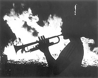 UTA homecoming; trumpet player silhouetted in front of bonfire, 1988-1989