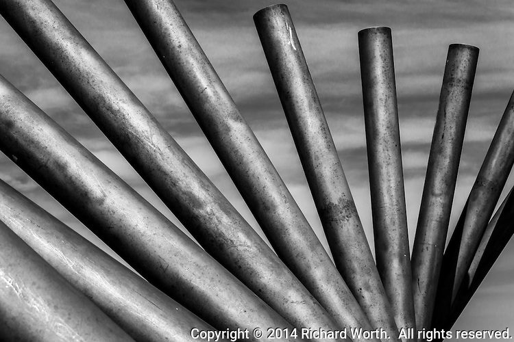 "In black and white, this photographer's interpretation of a sculptor's creation.  On a hill in Oyster Bay Regional Park, a sculpture of 10 foot poles rises.  The artist, sculptor, is Roger Berry.  From his website:   ""As you walk around the piece, the poles appear to cross. These crossed lines intersect with all the points on the horizon where the sun rises and sets throughout the year."""