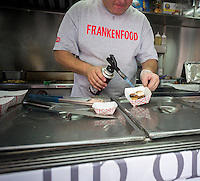 "The chef braises a Guinness Chocolate Coated Pork Belly, one of the creations of ""mash-up"" food from the Frankenfood truck in the Hudson Square neighborhood of New York on Friday, June 20, 2014. The truck is a promotion for Spike TV's ""Frankenfood"" program which features inventive culinary delights such as Spam Sushi, Braised Pork Belly S'mores and a number of other mis-matched treats.  Amateur chefs use unexpected ingredients on the television program and compete for top honors and cash.  (© Richard B. Levine)"