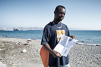 A refugee from Ivory Coast, who has been living in Turkey, will now try his luck in France or Germany. He is shown holding his papers from the Greek authorities. He stands at the coast line with life vests floating in the waters of the Mediterranean, and more strewn on the gravel beach. Kos, Greece. Sept. 6, 2015