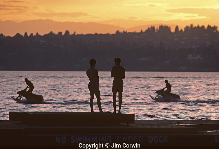 Lake Washington sunset with boys on dock silhouetted with two boys on jet skies Kirkland Washington State USA