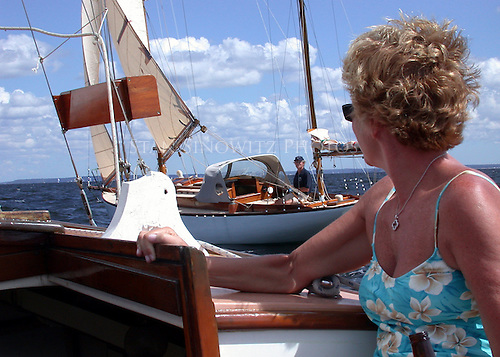 She is looking at a magnificently restore wooden sailboat and he is looking at a beautiful woman.