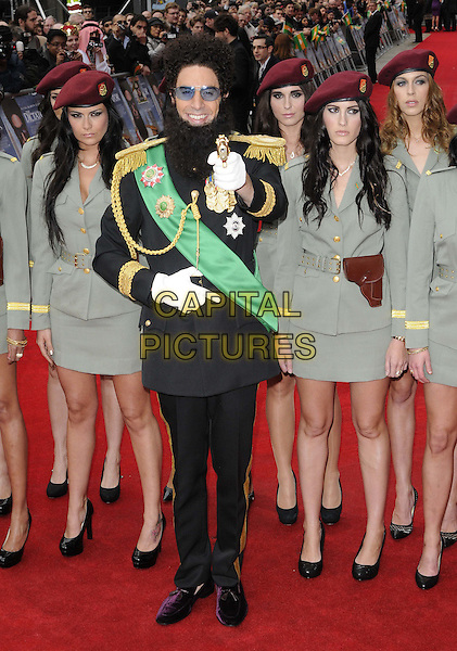 Sacha Baron Cohen.'The Dictator' world film premiere, Royal Festival Hall, London, England. .10th May 2012.full length black uniform suit green sash gold epaulettes beard facial hair girls grey gray skirt sunglasses shades  white gloves gun .CAP/CAN.©Can Nguyen/Capital Pictures.