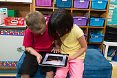 MR / Schenectady, NY. Zoller Elementary School (urban public school). Kindergarten inclusion classroom. Students read an eBook / app on an iPad. Left: boy, 5; Right: girl, 5. MR: Bur12, Coh2. ID: AM-gKw. © Ellen B. Senisi.
