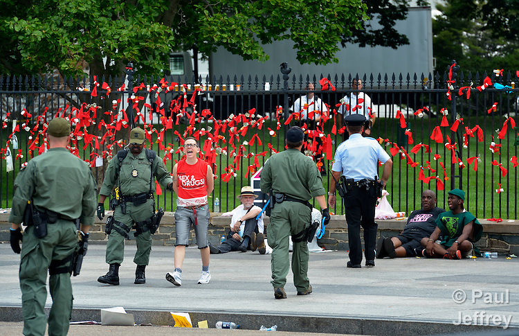 Protestors demonstrate outside the White House on July 24, 2012, criticizing U.S. support for pharmaceutical companies which have resisted generic licenses for their drugs for people living with HIV and AIDS. Several people were arrested after tying red ribbons, many connected to prescription bottles, onto the White House fence. The protest took place during the XIX International AIDS Conference.