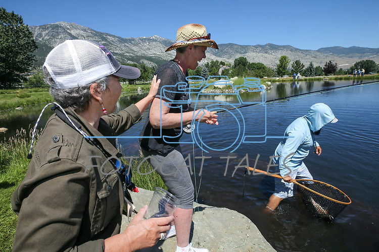 Diana Preston, left, congratulates Karen Kernan on her catch as cancer survivors learn to fly-fish during a Casting for Recovery retreat in Gardnerville, Nev., on Friday, June 30, 2017. Guide Jose Luna is at right. <br /> Photo by Cathleen Allison/Nevada Photo Source
