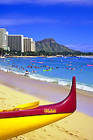Prow of a colorful outrigger canoe frames Diamond Head crater, condos and hotels, and swimmers at Waikiki Beach, an international vacation destination.