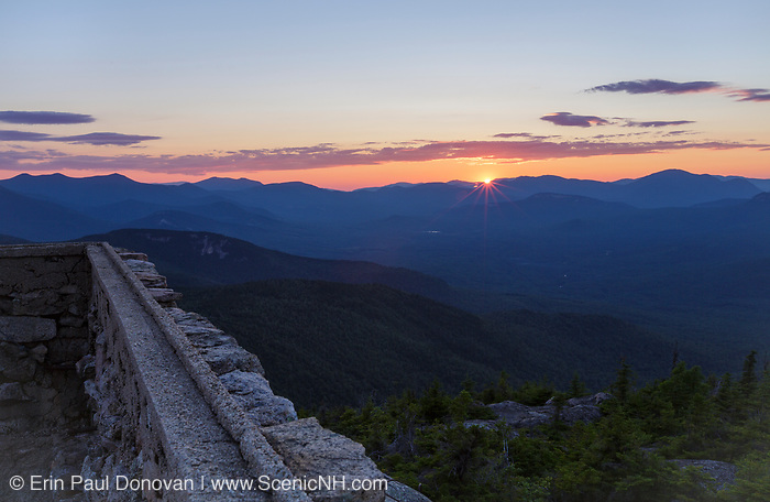 Sunset from Middle Sister Mountain in Albany, New Hampshire USA during the summer months. Remnants of the old Middle Sister fire tower are in the foreground.
