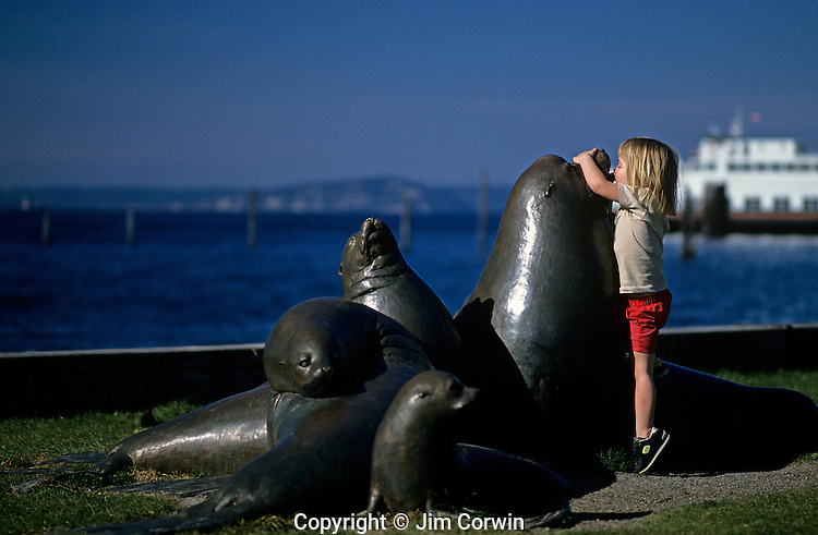 Washington State ferry on Puget Sound docked with child kissing sea lion sculpture along Edmonds waterfront Washington State USA