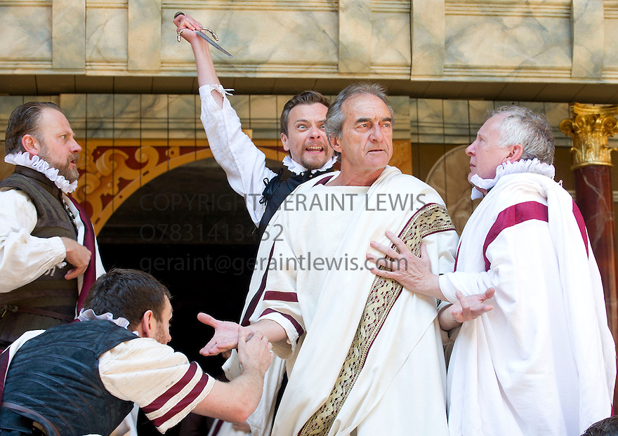 Julius Caesar by William Shakespeare. A Shakespeare's Globe Production directed by Dominic Dromgoogle. With George Irving as Julius Caesar, Christopher Logan as Casca [stabbing Caesar] . Opens at Shakespeare's Globe Theatre on 2/7/14  pic Geraint Lewis