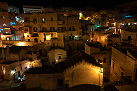 "Italy. Basilicata Region. Matera. At night, overall view on the historical centre. Known as la Città Sotterranea (""the Underground City""), Matera is one of the oldest continuously inhabited cities in the world, having been inhabited since the 10th millennium BC. Its historical centre ""Sassi"", along with the Park of the Rupestrian Churches, was awarded World Heritage Site status by UNESCO since 1993. The Sassi di Matera are two districts (Sasso Caveoso and Sasso Barisano), well-known for their ancient cave dwellings.The Sassi originate from a prehistoric troglodyte settlement and are suspected to be among the first human settlements in Italy. There is evidence that people were living here as early as the year 7000 BC.The Sassi are houses dug into the calcarenite rock itself, which is characteristic of Basilicata, locally called ""tufo"" although it is not volcanic tuff or tufa. The streets in some parts of the Sassi often run on top of other houses. The ancient town grew up on one slope of the ravine created by a river that is now a small stream. The ravine is known locally as ""la Gravina"". In the 1950s, the government of Italy forcefully relocated most of the population of the Sassi to areas of the developing modern city. Until the late 1980s this was considered an area of poverty, since many of these houses were, and in some cases still are, uninhabitable. The current local administration, however, has become more tourism-oriented, and it has promoted the regeneration of the Sassi with the aid of the European Union, the government, UNESCO. Today there are many thriving businesses, pubs, restaurants and hotels. On 17th October 2014, Matera was declared Italian host of European Capital of Culture for 2019. Basilicata is a region in Southern Italy. 8.12.18  © 2018 Didier Ruef"