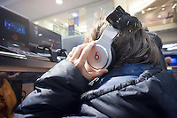 """A customer in a Best Buy store in New York listens on Beats by Dr. Dre headphones on Saturday, March 31, 2012. Beats Electronics, the maker of the high-end headphones """"Beats by Dr. Dre"""", is reported to be in the process of purchasing MOG.  (© Richard B. Levine)"""