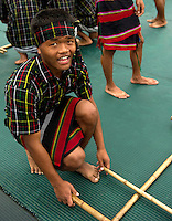 Boys in position for the dance at the Chapchar Kut  harvest festival celebrated in Mizoram, a state of North East India. At this festival, the Cheraw or bamboo dance is performed by young boys and girls. The boys across the performance ground clap bamboos in a synchronised beat, while the girls step within the bamboo patterns created by the boys. The footwork steps change from time to time along with the beat and the girls have to be careful not to get hurt. Image taken at Aizawl, Mizoram.
