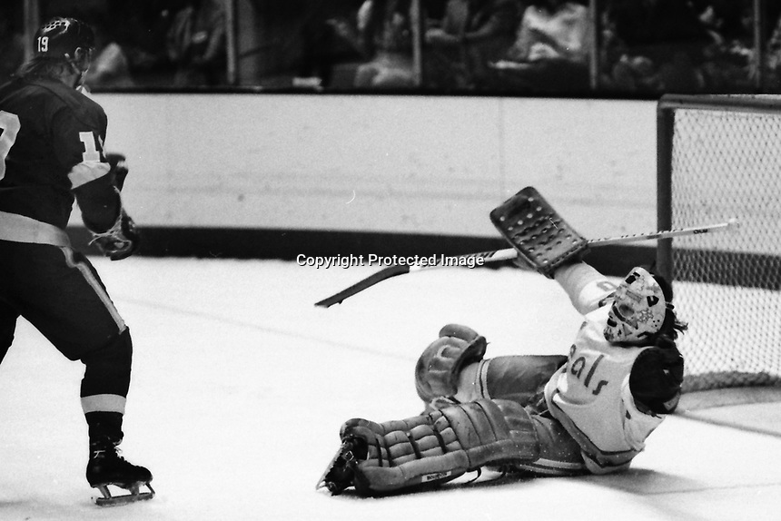 "Los Angles Kings #19 Robert ""Butch"" Goring scores goal against Seals goalie Gary Simmons. (1975 photo by Ron Riesterer)"